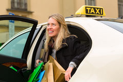La mujer joven sale del taxi Fotos de archivo libres de regalías