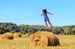 La mujer joven salta en pajar en un campo Ella manos separadas Cielo azul y árboles verdes en el fondo Paquetes grandes de heno foto de archivo libre de regalías