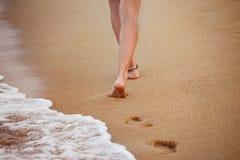 La mujer joven sana está caminando en la arena amarilla que sale del footpr Imagen de archivo libre de regalías