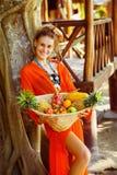 La mujer joven sana hermosa está sosteniendo la cesta de frui tropical Fotos de archivo libres de regalías