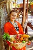 La mujer joven sana hermosa está sosteniendo la cesta de frui tropical Fotografía de archivo libre de regalías