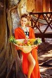 La mujer joven sana hermosa está sosteniendo la cesta de frui tropical Imagen de archivo