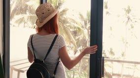 La mujer joven se acerca a la ventana de su nuevo apartamento almacen de metraje de vídeo