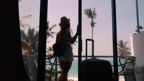 La mujer joven se acerca a la ventana de su nuevo apartamento almacen de video