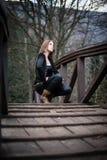 La mujer joven se agacha en el puente Foto de archivo libre de regalías