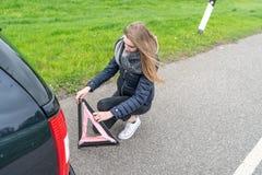 La mujer joven se arrodilla detrás del coche y monta el triángulo amonestador fotos de archivo