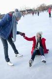La mujer joven se cae en el hielo mientras que patina, novio le ayuda para arriba Foto de archivo