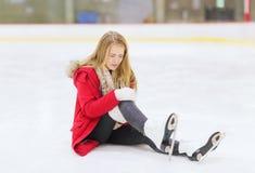 La mujer joven se cayó abajo en pista de patinaje foto de archivo libre de regalías