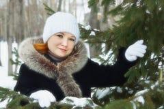 La mujer joven se coloca al lado de árbol de abeto en un parque del invierno al aire libre Fotografía de archivo libre de regalías