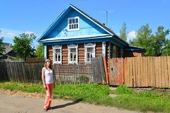 La mujer joven se coloca cerca de la casa de madera rural Foto de archivo libre de regalías