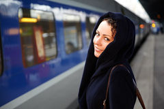 La mujer joven se coloca en el tren cercano de la plataforma Foto de archivo libre de regalías