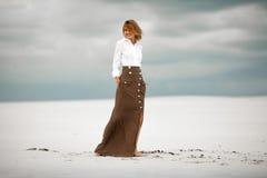 La mujer joven se coloca en la arena en desierto y sonríe Foto de archivo