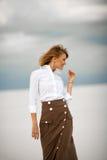 La mujer joven se coloca en la arena en desierto y sonríe Fotos de archivo