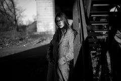 La mujer joven se coloca en sombra al lado de las escaleras Imagen blanco y negro fotografía de archivo