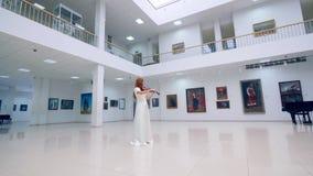 La mujer joven se coloca en un cuarto del museo y un violín de los juegos almacen de metraje de vídeo