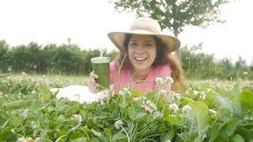 La mujer joven se divierte en el parque y bebe los smoothies verdes almacen de metraje de vídeo