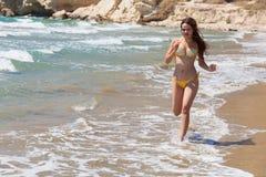 La mujer joven se ejecuta a lo largo de la playa Imagen de archivo