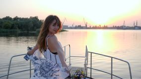 La mujer joven se está colocando en el arco del barco de vela en puesta del sol del fondo en viaje del verano