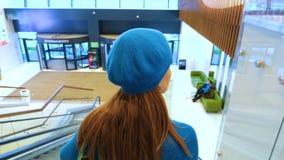 La mujer joven se está colocando en la escalera móvil en la alameda almacen de video