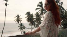 La mujer joven se está colocando en un balcón que pasa por alto el océano metrajes