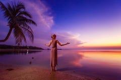 La mujer joven se está colocando relajada en la puesta del sol tropical azul profunda y Imagen de archivo