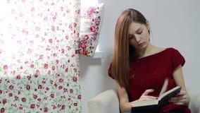 La mujer joven se está sentando en butaca y libro de lectura almacen de metraje de vídeo