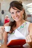 La mujer joven se está sentando en el café Foto de archivo
