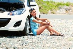 La mujer joven se está sentando en el camino cerca del coche Imágenes de archivo libres de regalías