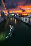 La mujer joven se está sentando en la cubierta durante puesta del sol Imagen de archivo