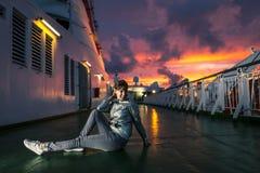 La mujer joven se está sentando en la cubierta durante puesta del sol Fotografía de archivo