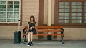 La mujer joven se está sentando en un banco en la plataforma de la estación y está leyendo un libro almacen de video