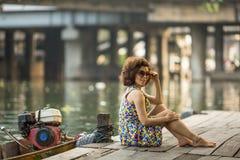 La mujer joven se está sentando en el terraplén de un río del ` s de la ciudad Fotografía de archivo