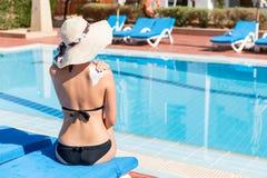 La mujer joven se est? sentando por la piscina y est? aplicando la crema del sol en su hombro por la piscina Factor de protecci?n foto de archivo