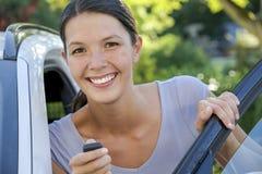 La mujer joven se inclina contra su coche Fotografía de archivo