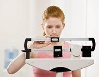 La mujer joven se pesa en la gimnasia Fotos de archivo