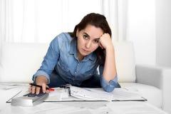 La mujer joven se preocupó en casa en considerar de la tensión desesperado en problemas financieros Foto de archivo