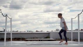 La mujer joven se prepara a la práctica de la yoga La muchacha presenta la estera de la yoga en el tejado en paisaje urbano metrajes
