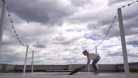 La mujer joven se prepara a la práctica de la yoga y a poner su estera de la yoga en la cámara lenta metrajes