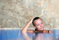 La mujer joven se refresca apagado en piscina Imagenes de archivo