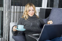 La mujer joven se relaja con la computadora portátil Fotografía de archivo libre de regalías