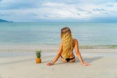 La mujer joven se relaja con las piñas en la playa Imagen de archivo