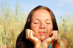 La mujer joven se relaja en campo verde Imágenes de archivo libres de regalías