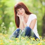 La mujer joven se relaja en el parque con las flores Escena de la naturaleza de la belleza Foto de archivo libre de regalías