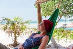 La mujer joven se relaja en la playa Imagen de archivo libre de regalías