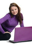 La mujer joven se sienta con el cuaderno púrpura. imagenes de archivo