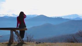 La mujer joven se sienta en banco afuera y mirada en el paisaje ilustrado con las montañas almacen de metraje de vídeo