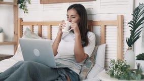 La mujer joven se sienta en cama, bebe el café y trabaja en el ordenador portátil en el dormitorio, cámara lenta almacen de metraje de vídeo