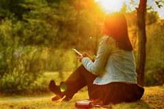 La mujer joven se sienta en el parque Imagenes de archivo