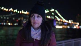 La mujer joven se sienta en el puente de Brooklyn Nueva York por noche metrajes