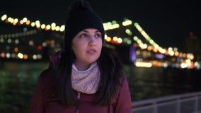 La mujer joven se sienta en el puente de Brooklyn Nueva York por noche almacen de video